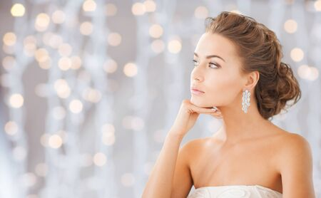 Photo pour people, holidays, wedding, jewelry and luxury concept - beautiful woman wearing shiny diamond earrings over lights background - image libre de droit