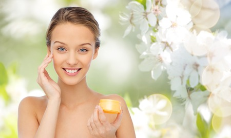 Photo pour beauty, people, cosmetics, skincare and cosmetics concept - happy young woman applying cream to her face over summer green natural background with cherry blossom - image libre de droit
