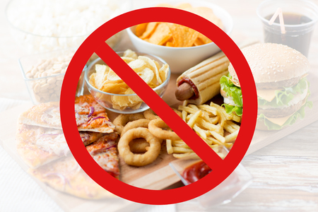 Photo pour fast food, low carb diet, fattening and unhealthy eating concept - close up of fast food snacks and cola drink on wooden table behind no symbol or circle-backslash prohibition sign - image libre de droit