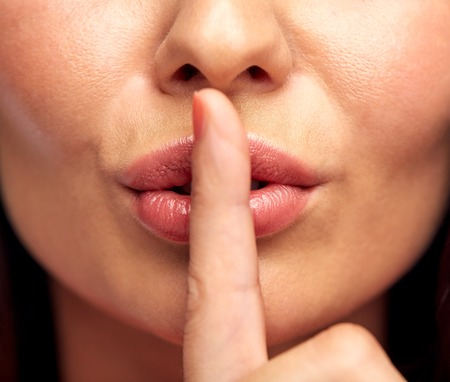 Foto de silence, gesture and beauty concept - close up of young woman holding finger on lips - Imagen libre de derechos