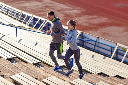 Photo pour fitness, sport, exercising and lifestyle concept - couple running upstairs on stadium - image libre de droit