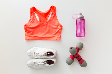 Foto de sport, fitness, healthy lifestyle and objects concept - close up of female sports clothing, dumbbells and bottle set - Imagen libre de derechos