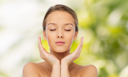 Foto de beauty, people, skincare and health concept - young woman face and hands over green natural background - Imagen libre de derechos