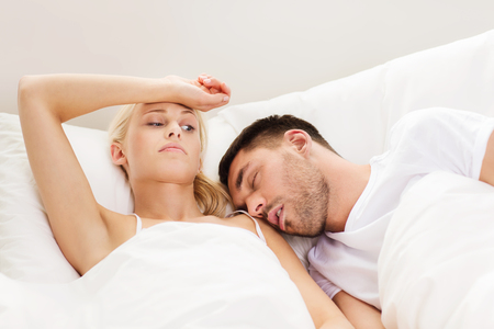 Photo pour people, family, bedtime and insomnia concept - unhappy woman having sleepless night with sleeping and snoring man in bed at home - image libre de droit