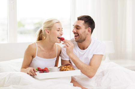 Photo pour people, love, care and happiness concept - happy couple having breakfast in bed and eating strawberries at home - image libre de droit