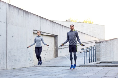 Photo for fitness, sport, people, exercising and lifestyle concept - man and woman skipping with jump rope outdoors - Royalty Free Image