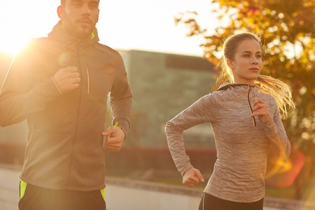 Foto de fitness, sport, people and lifestyle concept - couple running outdoors - Imagen libre de derechos
