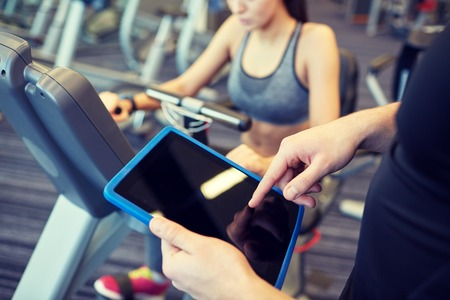 Foto de sport, fitness, lifestyle, technology and people concept - close up of trainer hands with tablet pc computer and woman working out on exercise bike in gym - Imagen libre de derechos