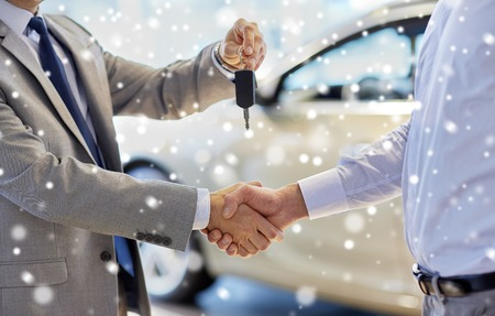 Foto de auto business, car sale, deal, gesture and people concept - close up of dealer giving key to new owner and shaking hands in auto show or salon over snow effect - Imagen libre de derechos