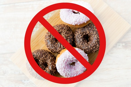 Photo for fast food, low carb diet, fattening and unhealthy eating concept - close up of glazed donuts on wooden board behind no symbol or circle-backslash prohibition sign - Royalty Free Image