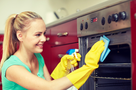 Photo pour people, housework and housekeeping concept - happy woman with bottle of spray cleanser cleaning oven at home kitchen - image libre de droit