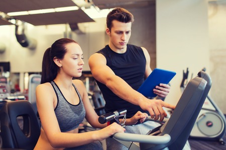 Foto de sport, fitness, lifestyle, technology and people concept - woman with trainer working out on exercise bike in gym - Imagen libre de derechos
