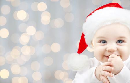Foto de christmas, babyhood, childhood and people concept - happy baby in santa hat over holidays lights background - Imagen libre de derechos