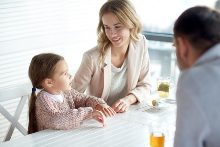 Foto de family, parenthood, communication and people concept - happy mother, father and little girl having dinner and talking at restaurant or cafe - Imagen libre de derechos