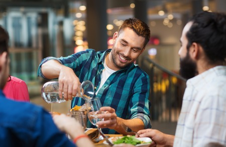 Photo pour leisure, people and holidays concept - smiling man with friends pouring water from jug at restaurant - image libre de droit