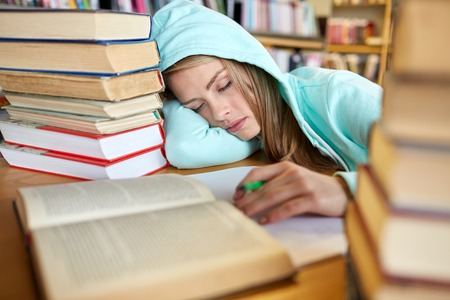 Foto de people, education, session, exams and school concept - tired student girl or young woman with books sleeping in library - Imagen libre de derechos