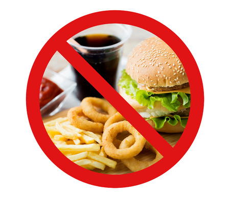 Foto de fast food, low carb diet, fattening and unhealthy eating concept - close up of hamburger or cheeseburger, deep-fried squid rings and french fries behind no symbol or circle-backslash prohibition sign - Imagen libre de derechos