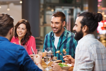 Photo for leisure, food and drinks, people and holidays concept - happy friends having dinner at restaurant - Royalty Free Image