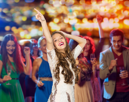 Foto de people, holidays and nightlife concept - happy young woman or teen girl in fancy dress with sequins and long wavy hair dancing at night club party over crowd and lights background - Imagen libre de derechos