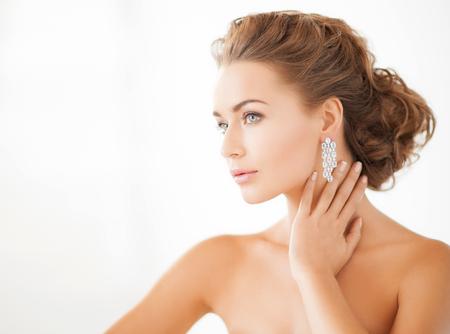 Photo pour beauty and jewelery concept - woman wearing shiny diamond earrings - image libre de droit