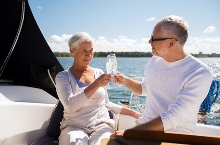 Foto de sailing, age, travel, holidays and people concept - happy senior couple clinking champagne glasses on sail boat or yacht deck floating in sea - Imagen libre de derechos