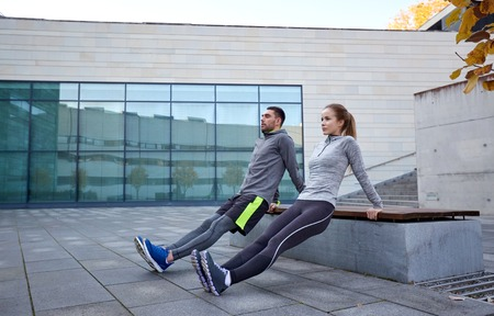 Photo for fitness, sport, training, people and lifestyle concept - couple doing triceps dip exercise on bench outdoors - Royalty Free Image
