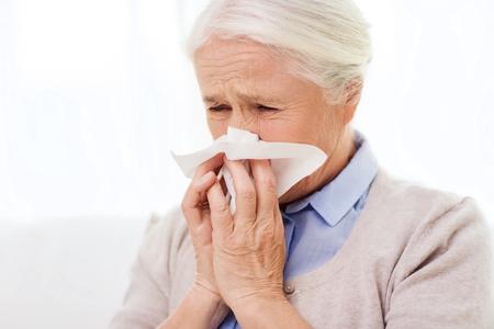 Photo pour sick senior woman blowing nose to paper napkin at home - image libre de droit