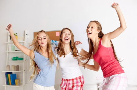 Photo for happy friends or teenage girls having fun and jumping on bed at home - Royalty Free Image