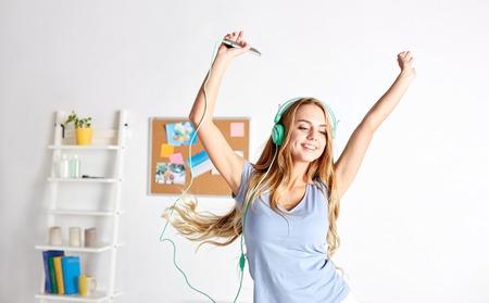 Foto de happy woman or teenage girl in headphones listening to music from smartphone and dancing on bed at home - Imagen libre de derechos