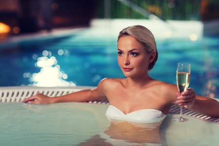 Foto de beautiful young woman wearing bikini swimsuit sitting with glass of champagne in jacuzzi at poolside - Imagen libre de derechos