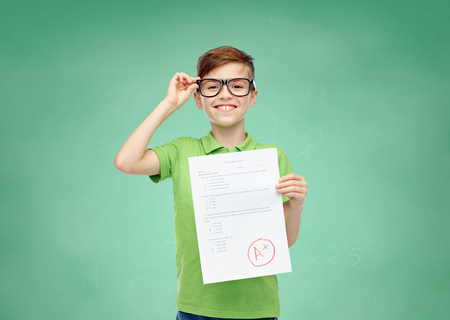 Photo pour happy smiling boy in eyeglasses holding paper with test result over green school chalk board background - image libre de droit