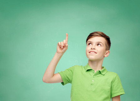 Photo pour happy smiling boy in green polo t-shirt pointing finger up over green school chalk board background - image libre de droit
