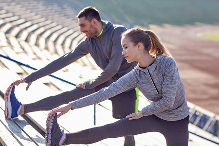 Photo for couple stretching leg on stands of stadium - Royalty Free Image