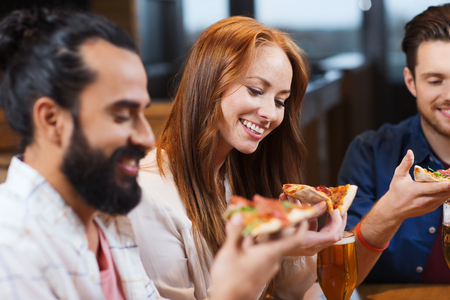 Photo for smiling friends eating pizza and drinking beer at restaurant or pub - Royalty Free Image