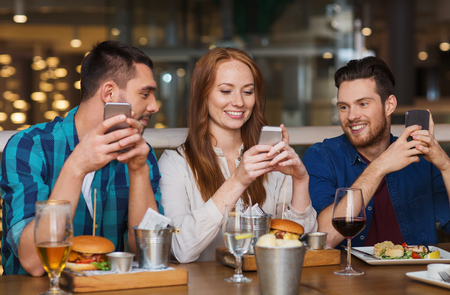 Photo for happy friends with smartphones dining at restaurant - Royalty Free Image