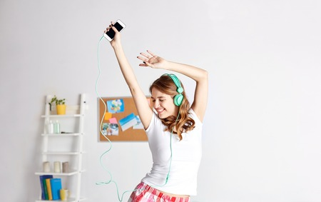 happy woman or teenage girl in headphones listening to music from smartphone and dancing on bed at home