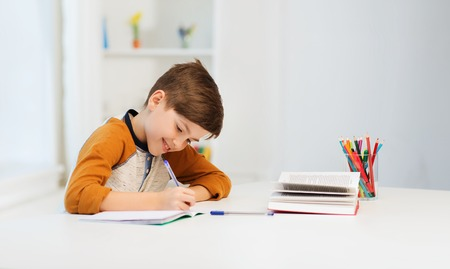 Photo for education, childhood, people, homework and school concept - smiling student boy with book writing to notebook at home - Royalty Free Image