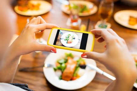 Photo pour people, leisure, technology and internet addiction concept - close up of woman with smartphone photographing food at restaurant - image libre de droit