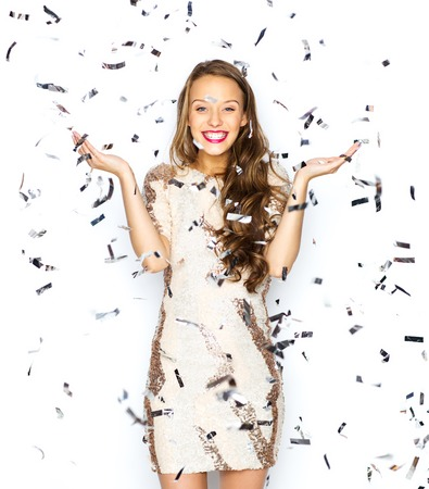 Photo for people, holidays, emotion and glamour concept - happy young woman or teen girl in fancy dress with sequins and confetti at party - Royalty Free Image