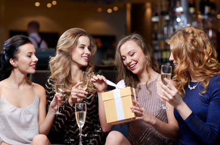 Foto de celebration, friends, bachelorette party, birthday and holidays concept - happy women with champagne glasses and gift box at night club - Imagen libre de derechos