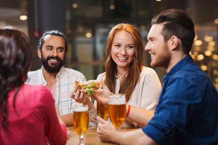 Foto per leisure, food and drinks, people and holidays concept - smiling friends eating pizza and drinking beer at restaurant or pub - Immagine Royalty Free