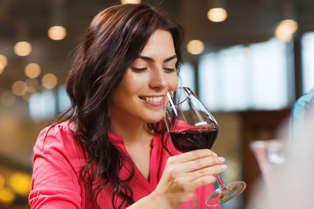 Photo pour leisure, drinks, degustation, people and holidays concept - smiling woman drinking red wine at restaurant - image libre de droit