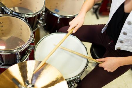 Photo for music, sale, people, musical instruments and entertainment concept - close up of female musician playing cymbals on drum kit - Royalty Free Image