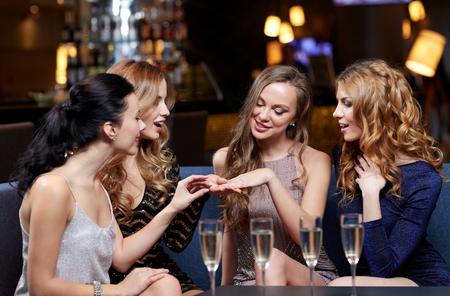 Photo pour celebration, friends, bachelorette party and holidays concept - happy woman showing engagement ring to her friends with champagne glasses at night club - image libre de droit