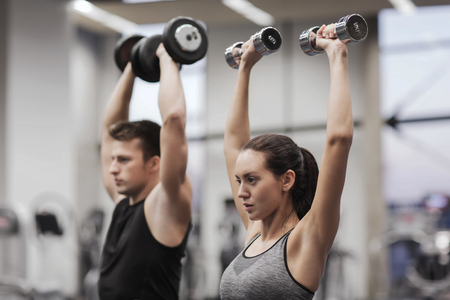 Photo for sport, fitness, lifestyle and people concept - smiling man and woman with dumbbells flexing muscles in gym - Royalty Free Image