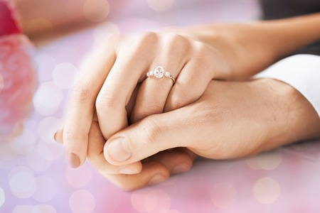Photo pour people, holidays, engagement and love concept - close up of engaged couple holding hands with diamond ring over holidays lights background - image libre de droit