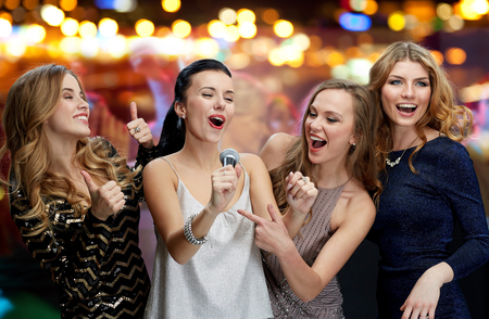 Photo for holidays, friends, bachelorette party, nightlife and people concept - three women in evening dresses with microphone singing karaoke over night club disco lights background - Royalty Free Image
