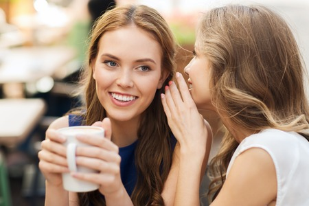 Foto de people communication and friendship concept - smiling young women drinking coffee or tea and gossiping at outdoor cafe - Imagen libre de derechos