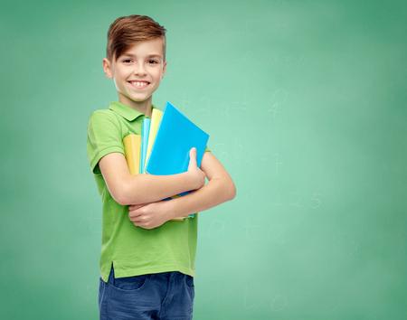 Foto de childhood, school, education and people concept - happy smiling student boy with folders and notebooks over green school chalk board background - Imagen libre de derechos