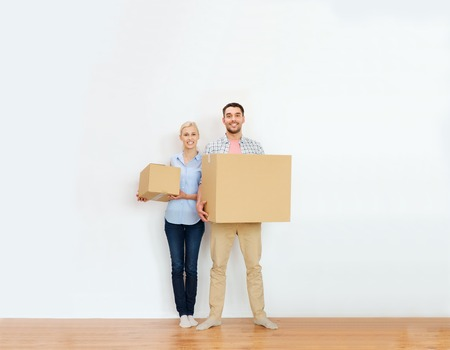 Photo for home, people, repair and real estate concept - happy couple holding cardboard boxes and moving to new place - Royalty Free Image